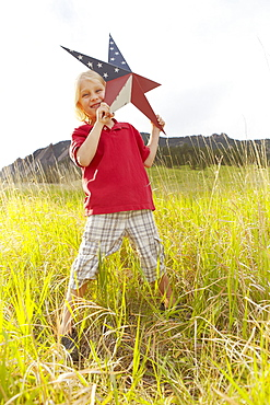 Boy (6-7) playing with star with American flag pattern