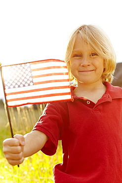 Portrait of boy (6-7) waving American flag in meadow