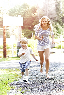 Mother and son (2-3) running on footpath