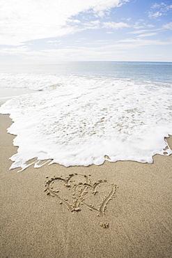 USA, Massachusetts, Hearts drawn on sandy beach