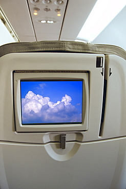 Airplane seat with monitor displaying clouds