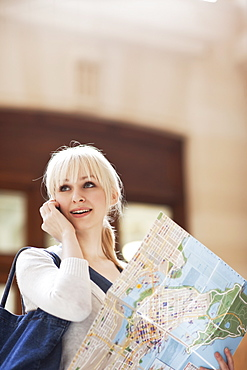 USA, Seattle, Young woman talking via phone and holding map