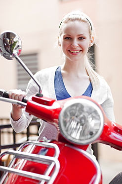 USA, Seattle, Young smiling woman on scooter, portrait
