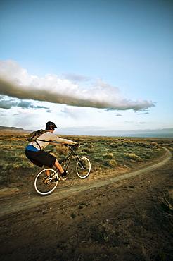Man mountain biking on dirt track