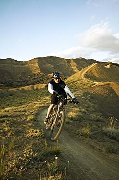 Man mountain biking on mountain track