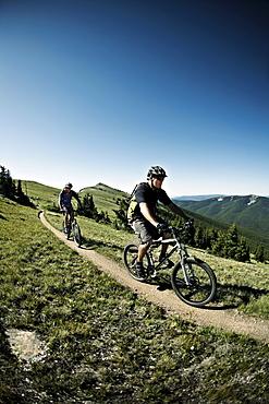Men mountain biking on mountain track