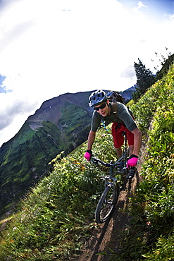 Man mountain biking on trail