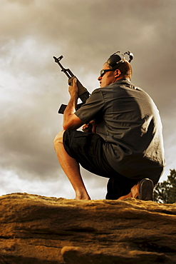 Man holding gun on rocks
