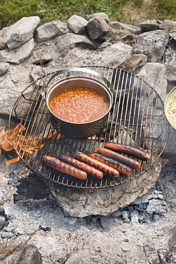 Grilled sausages and beans on campfire