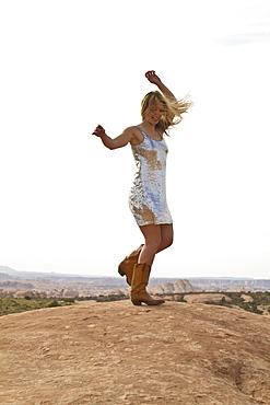 Young woman dancing on rocks