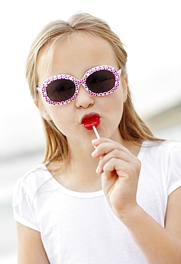 Girl (10-11) wearing sunglasses on beach is licking lollypop