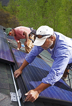 Construction workers installing solar panels on roof