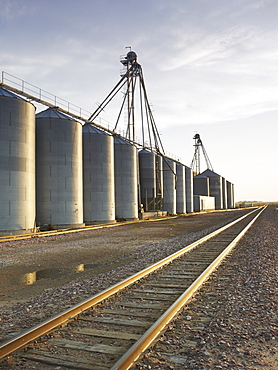 Train tracks beside silos