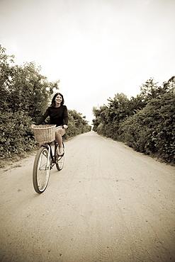 Woman biking on small rural road