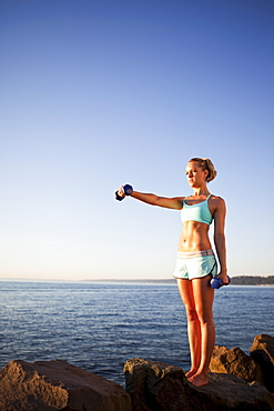 Athletic woman lifting weights outdoors