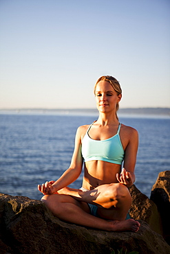 Athletic woman meditating by the ocean