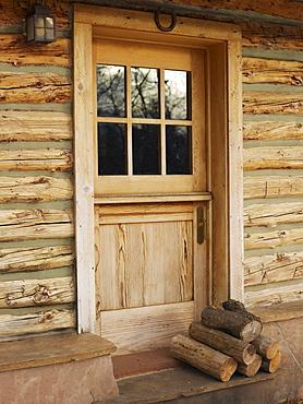 Firewood in front of door of log cabin