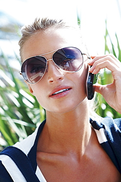 Blond woman wearing sunglasses and talking on phone