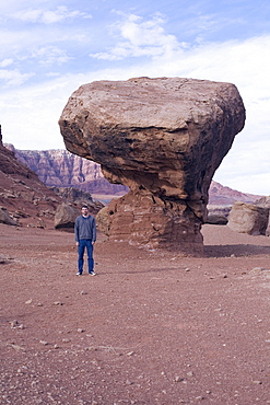 Tourist in front of butte in Arizona desert