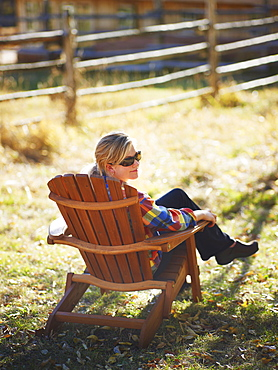 Woman sitting in Adirondack chair