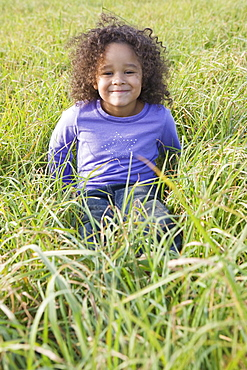 Young girl sitting in tall grass