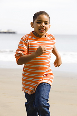 Young boy running on beach