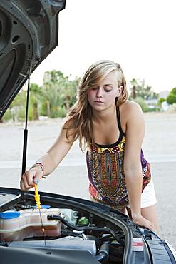 Woman checking car's oil