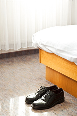 Shoes in front of bed