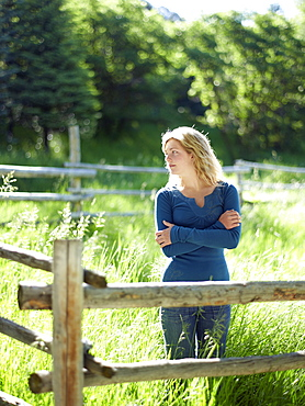 Young woman behind fence