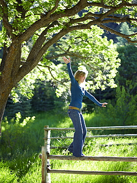 Young woman balancing on fence