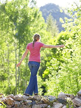 Woman walking on stone barrier