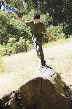 Young male balancing on log
