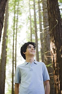 Smiling boy behind tree