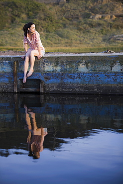 A woman sitting on a stone wall by water