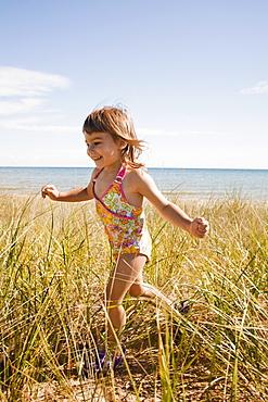 Beaver Island, Girl running in grass on beach, Beaver Island, Michigan, USA