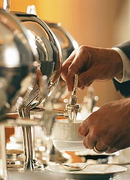 Man pouring tea from samovar