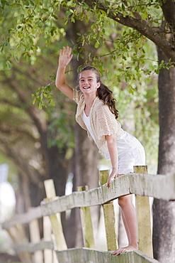 Girl standing on fence waving