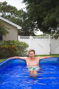 Portrait of man soaking in inflatable swimming pool