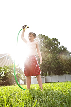 Boy spraying himself with hose in backyard