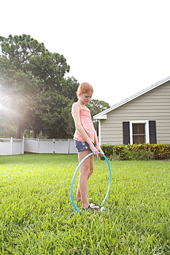 Girl standing in backyard with hula hoop