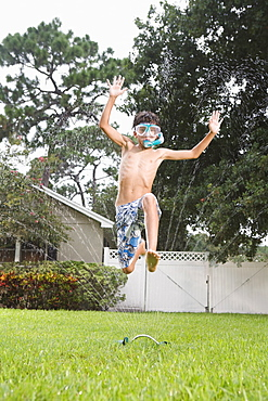 Boy with snorkeling mask running through sprinkler