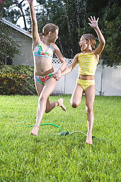 Sisters in bathing suits running through sprinkler