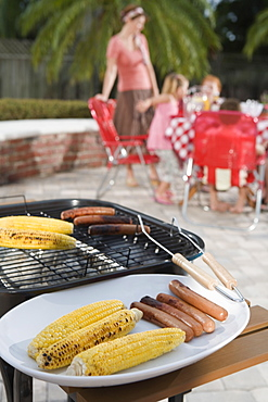 Grilled hotdogs and corn on backyard grill