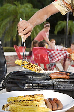 Man grilling hotdogs and corn in backyard