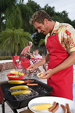 Man grilling hotdogs and corn in backyard