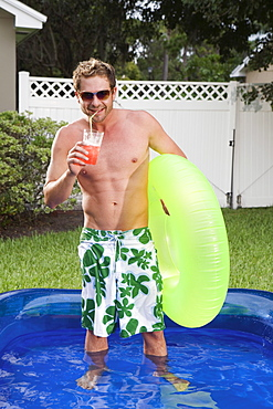 Man standing in inflatable swimming pool