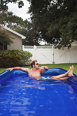 Man relaxing in inflatable swimming pool