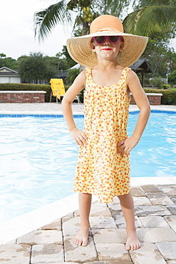 Sassy girl standing at edge of swimming pool
