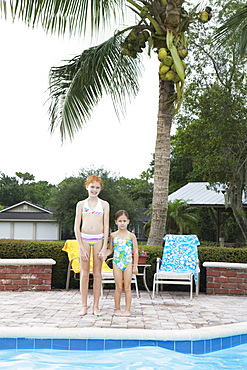 Girls standing at edge of swimming pool