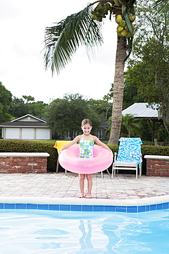 Girl standing at edge of swimming pool with inflatable ring